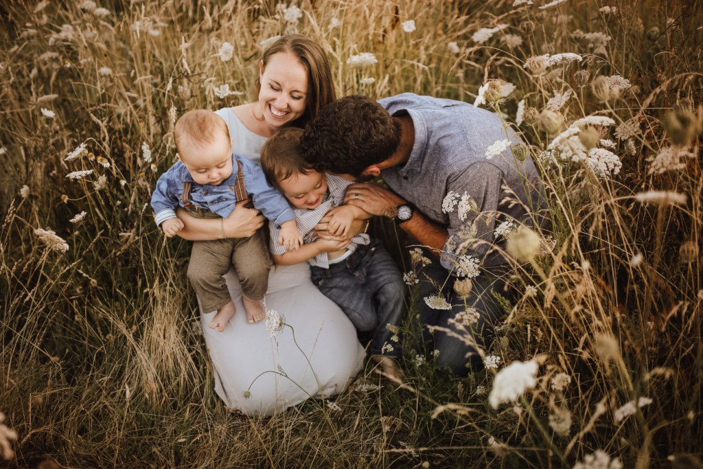 Victoria BC Family Photographer. Photo of family of 4, with Mum Dad and 2 young boys in a field laughing